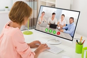 45696173 - young woman videoconferencing with colleagues on computer at desk