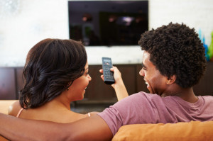 33474091 - rear view of couple sitting on sofa watching tv together