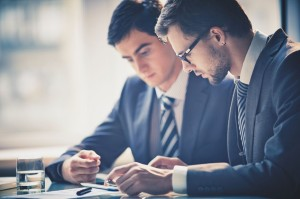 23245353 - image of two young businessmen using touchpad at meeting
